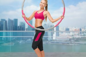 Young sporty woman wihth hula hoop