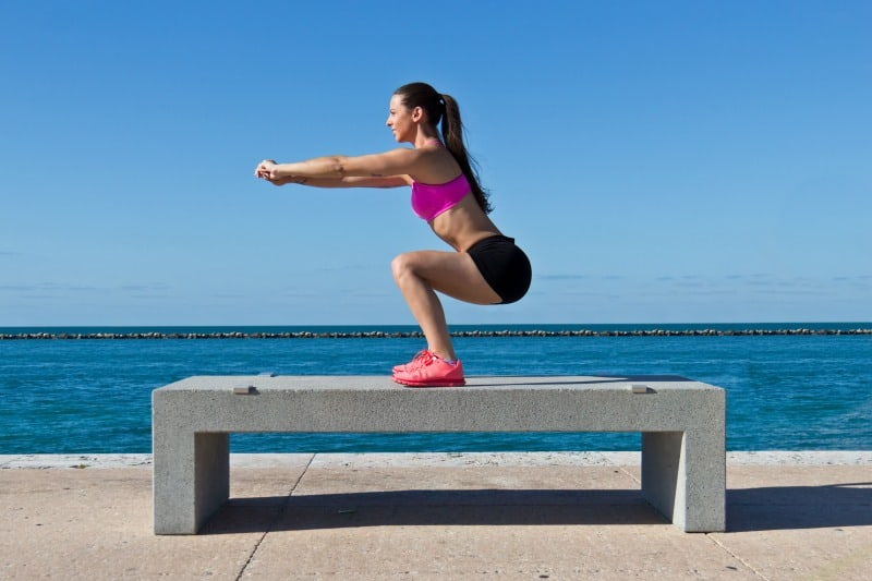 Hispanic woman doing squats on a bench by the ocean
