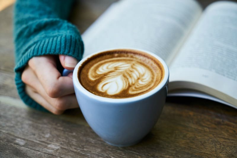Girl reading with a cup of coffee