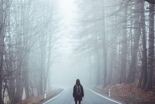 A girl lost on a foggy road