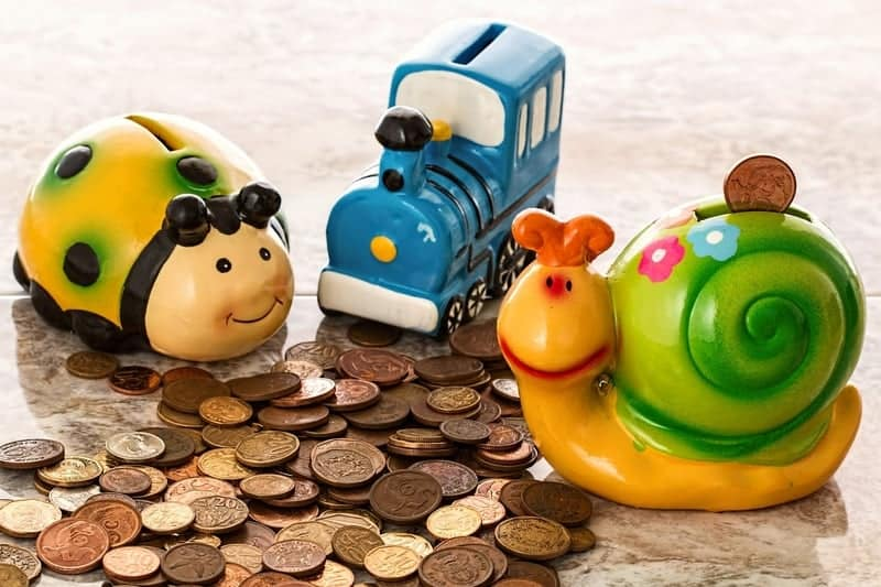 Cute animal piggy banks and lots of coins