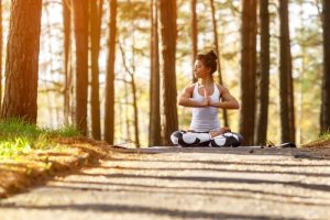 Woman in yoga pose, surraounded by beautiful autumn scenery