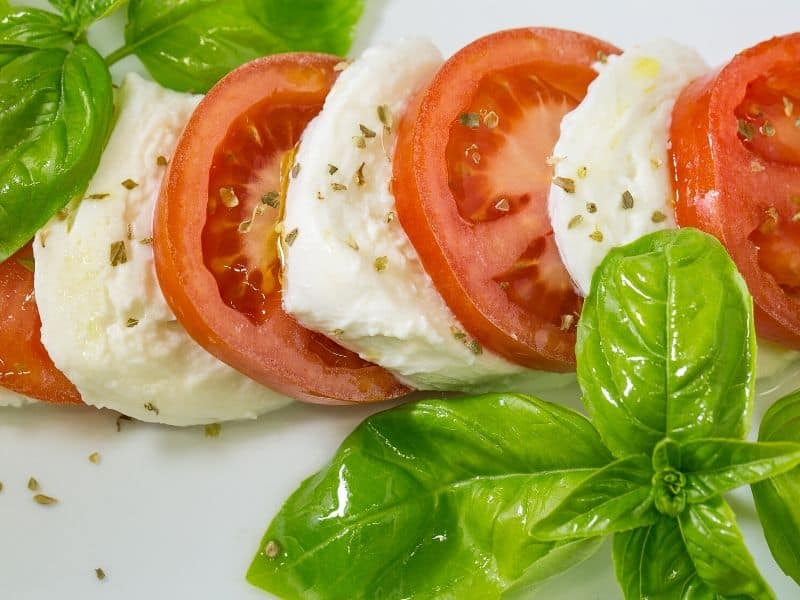 Fresh mozarella and tomatoes with basil leaves