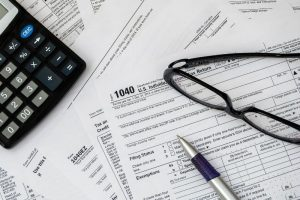 Tax forms, calculator and glasses
