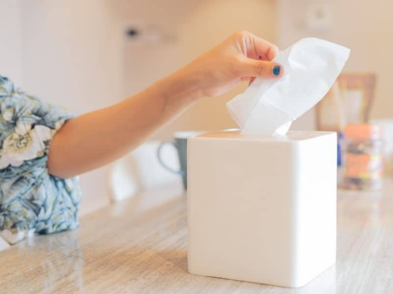 Woman pulling a tissue out of a tissue box