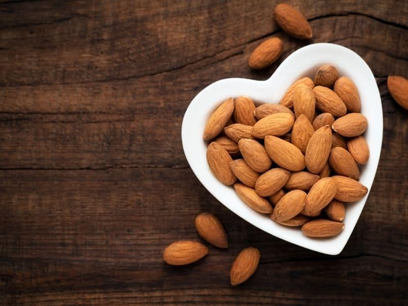 A heart shaped bowl filled with almonds