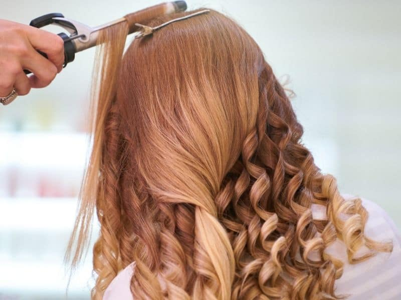 Girl using a curling iron to curl her hair