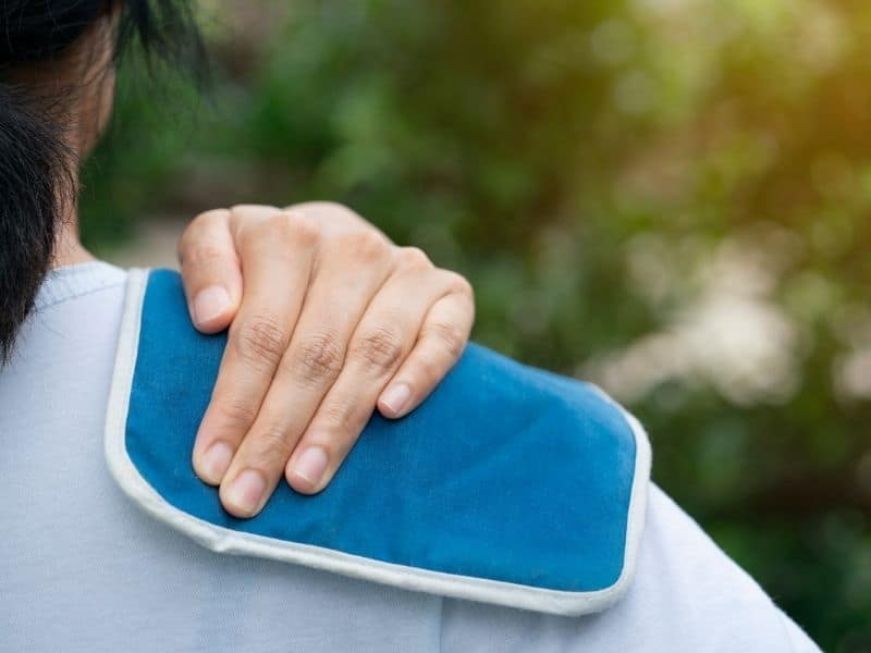 woman holding an ice pack on her shoulder