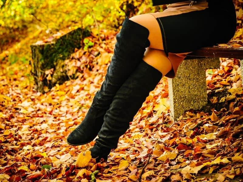 Woman wearing knee high boots sitting on a bench in the fall