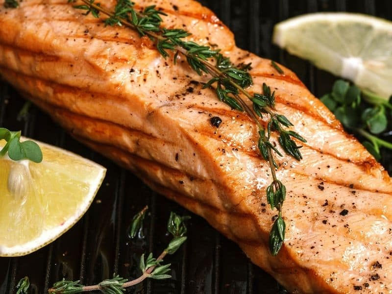 Cooked salmon on the plate with a lemon wedge