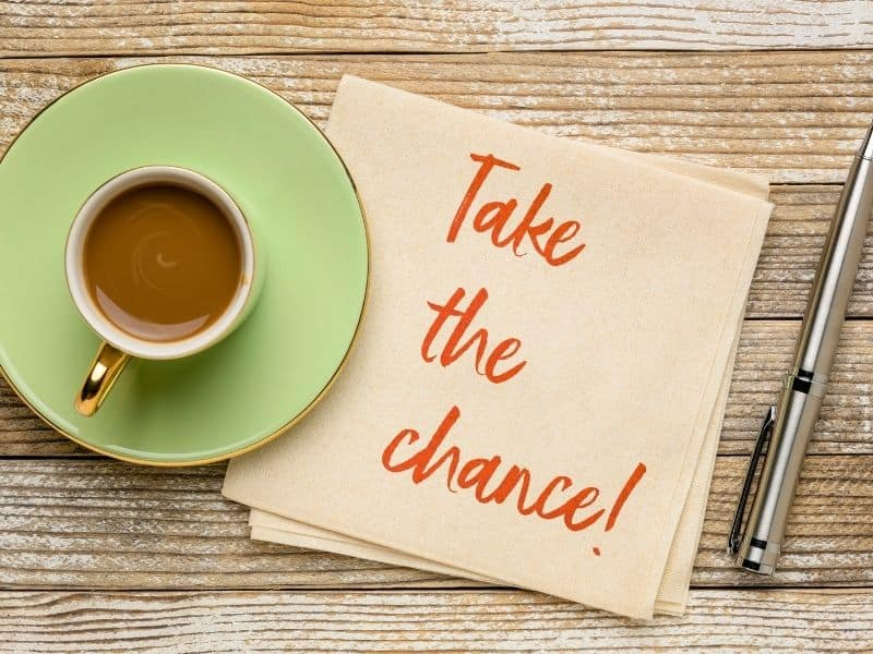 Take the chance written on a napkin, next to a bright green coffe mug