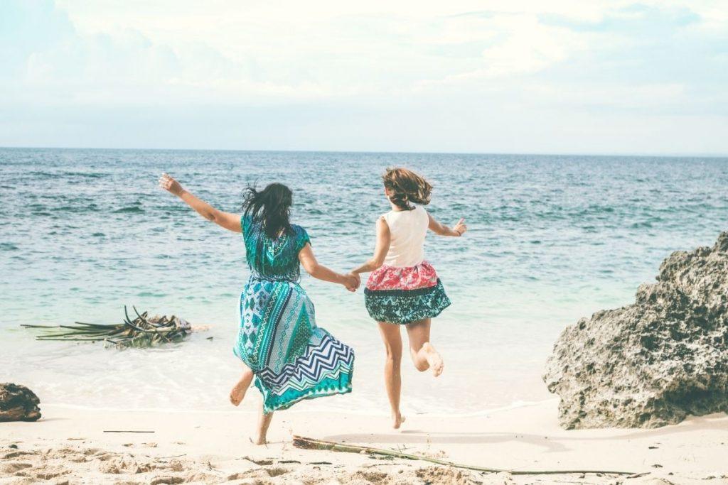 girlfriends running on the beach