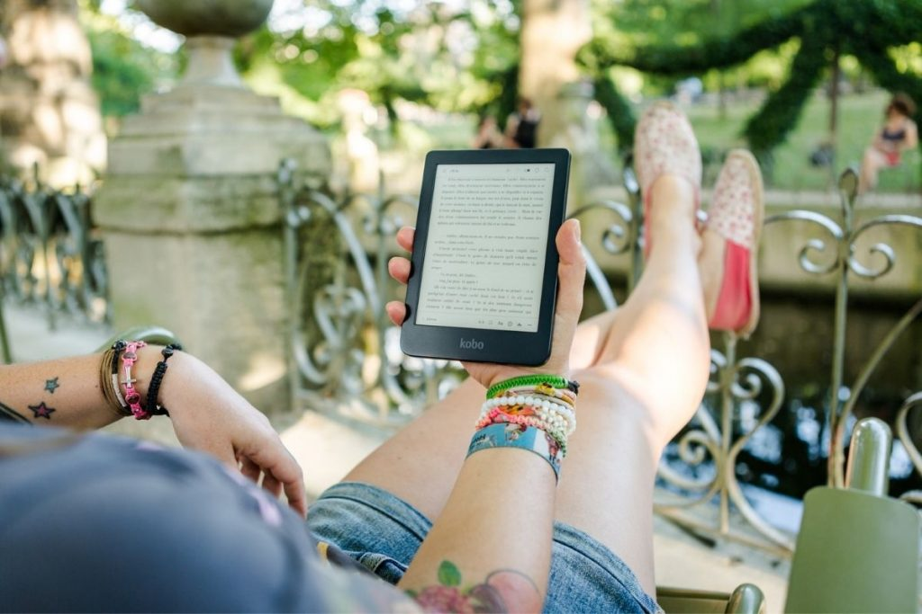 woman sitting outside reading on her digital reader